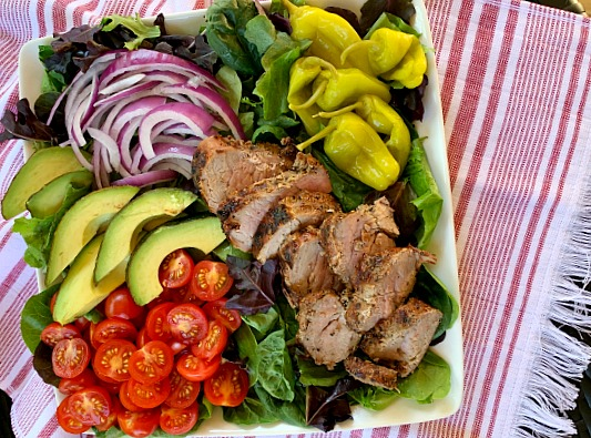 Fire up the grill for this delicious and light recipe for garlic and cracked black pepper grilled pork tenderloin salad with loads of toppings. A great grilling recipe for summer!